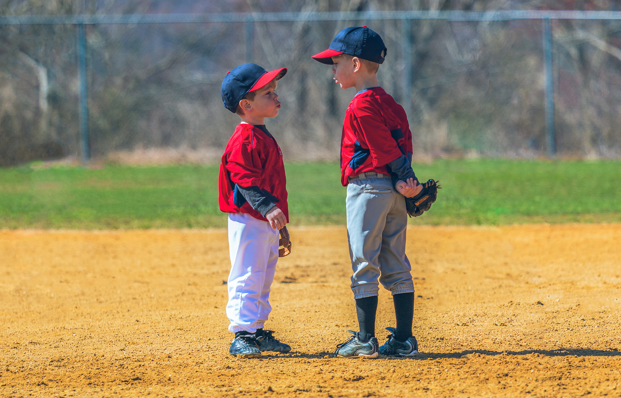 Two boys, unfocused on their baseball game, have fun whistling.