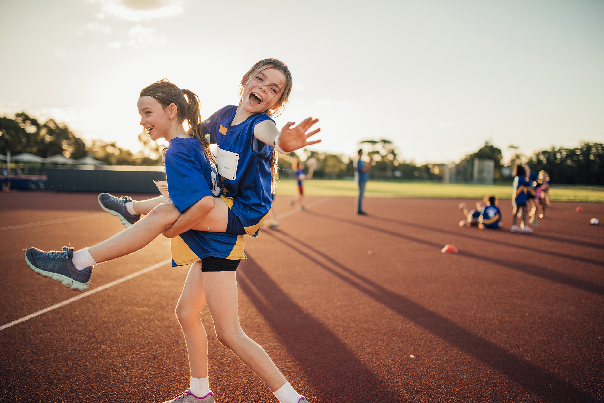 Two girls are messing around at athletics club on the running track. One is giving the other a piggy back and she is reaching out for the camera.