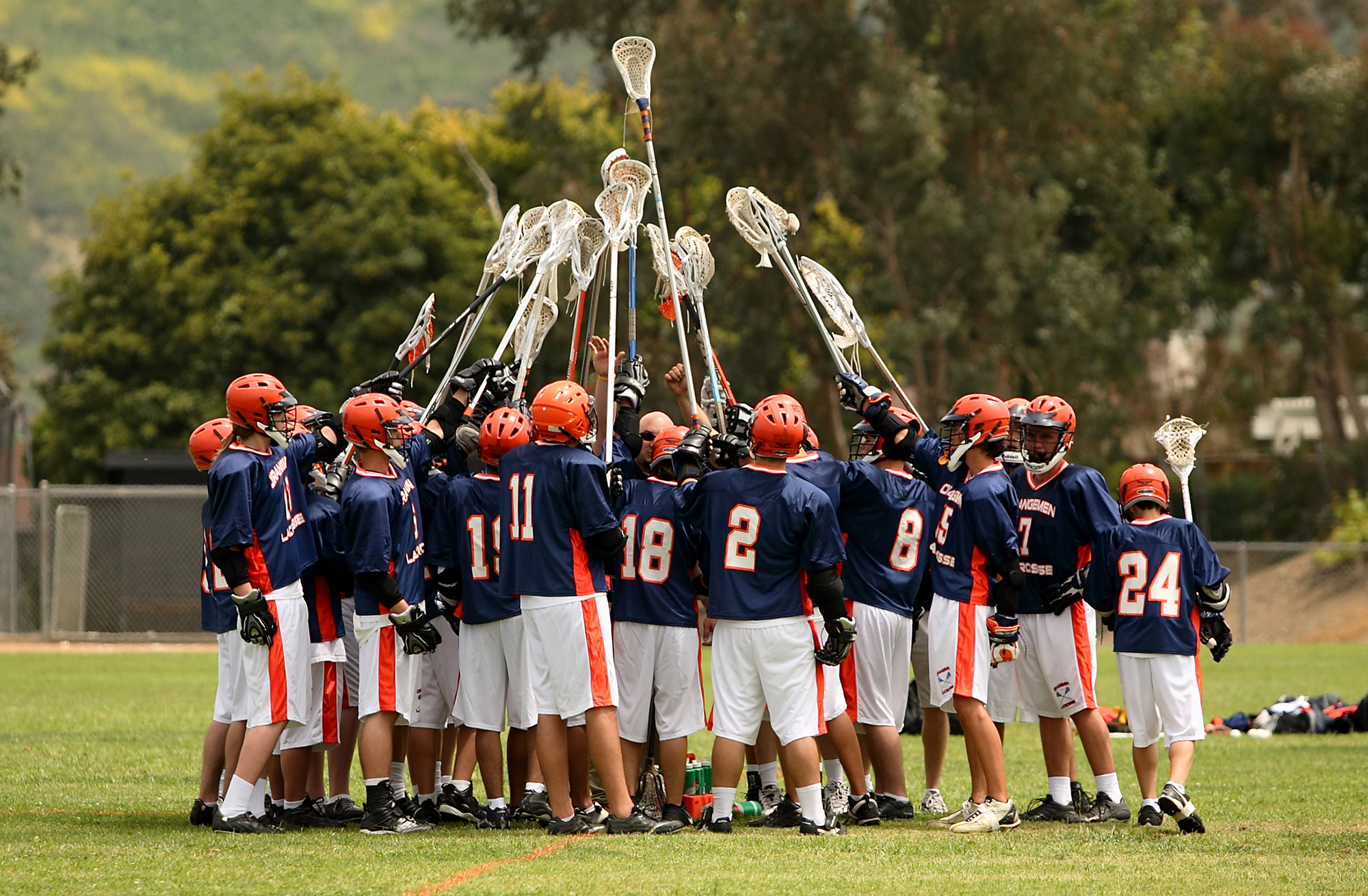 Image of a lacrosse team holding their stick up high prior to the start of the game.