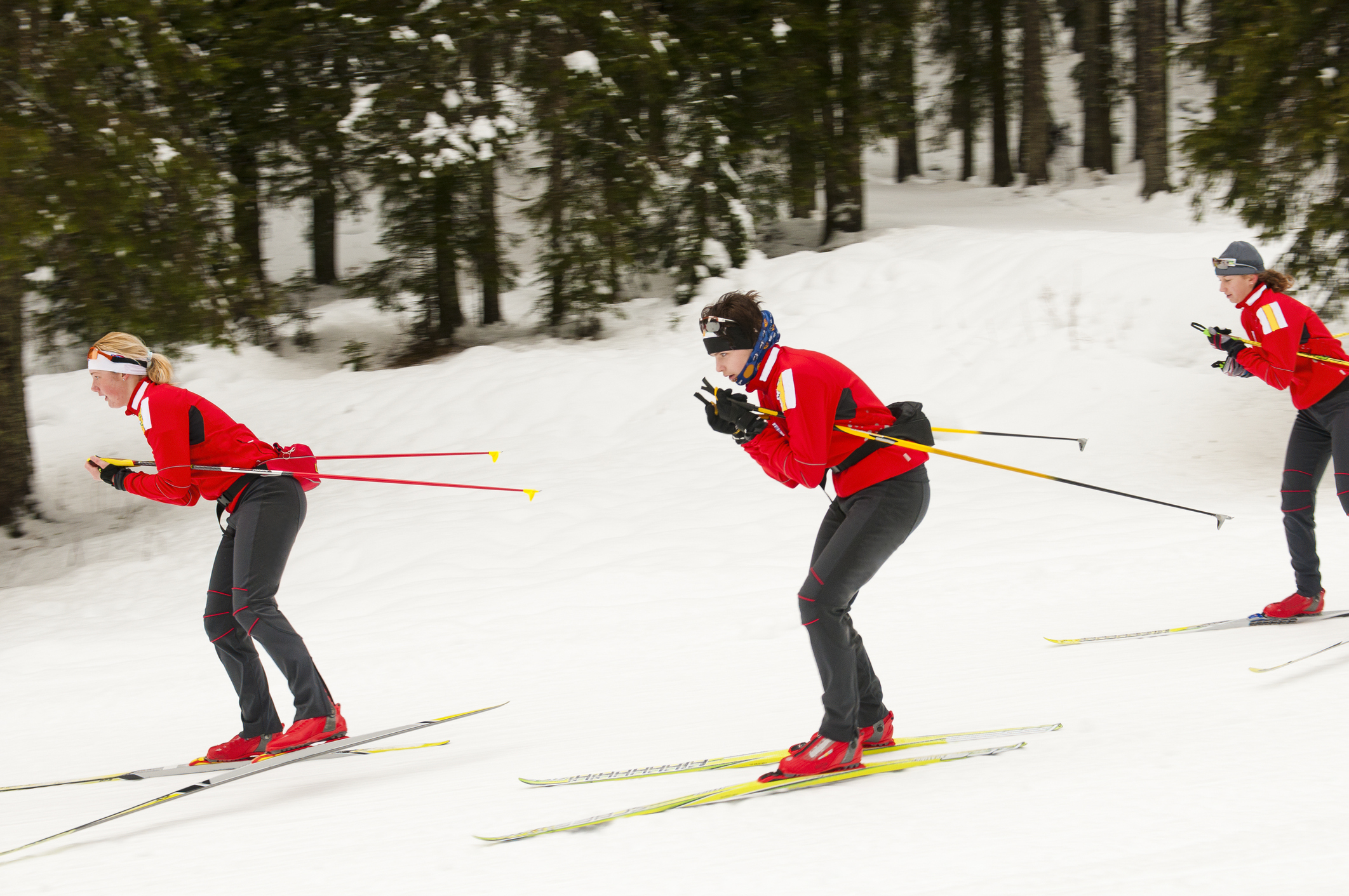 """""""Three young female cross country skiers at downhill, skating style"""""""