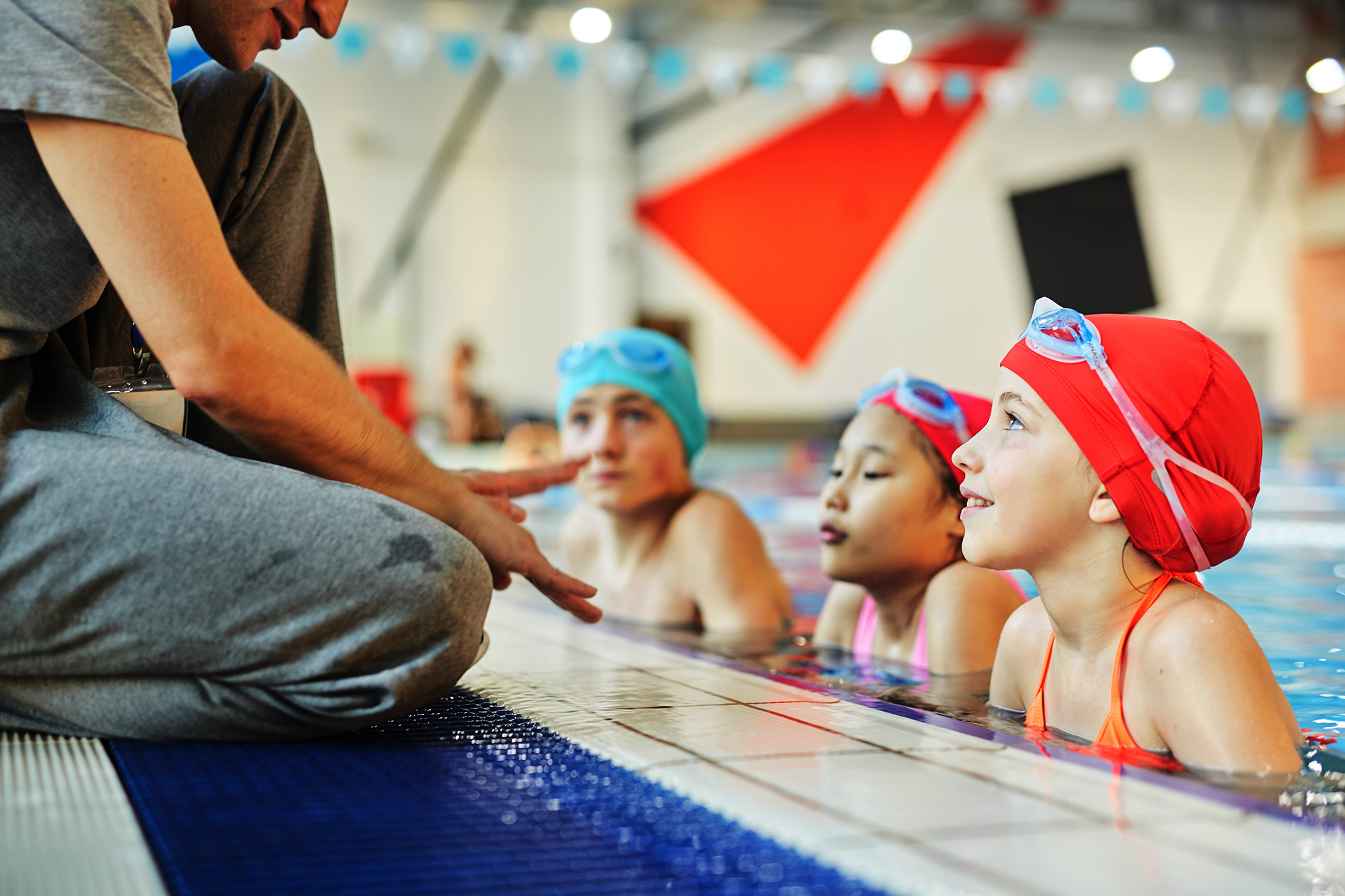 Cute swimmer and her groupmates in water listening to trainer instructions during training