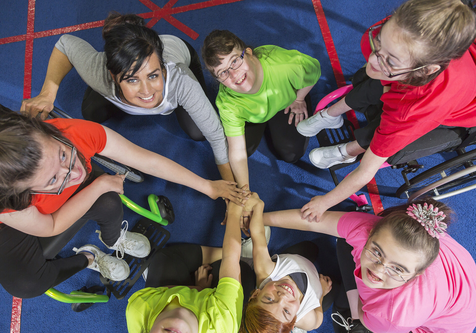 Overhead view of a group of special needs teenagers and young women with instructor, showing team spirit. They are sitting in a circle on a gym floor, hands in the center. Several of the girls have downs syndrome and two are in wheelchairs.