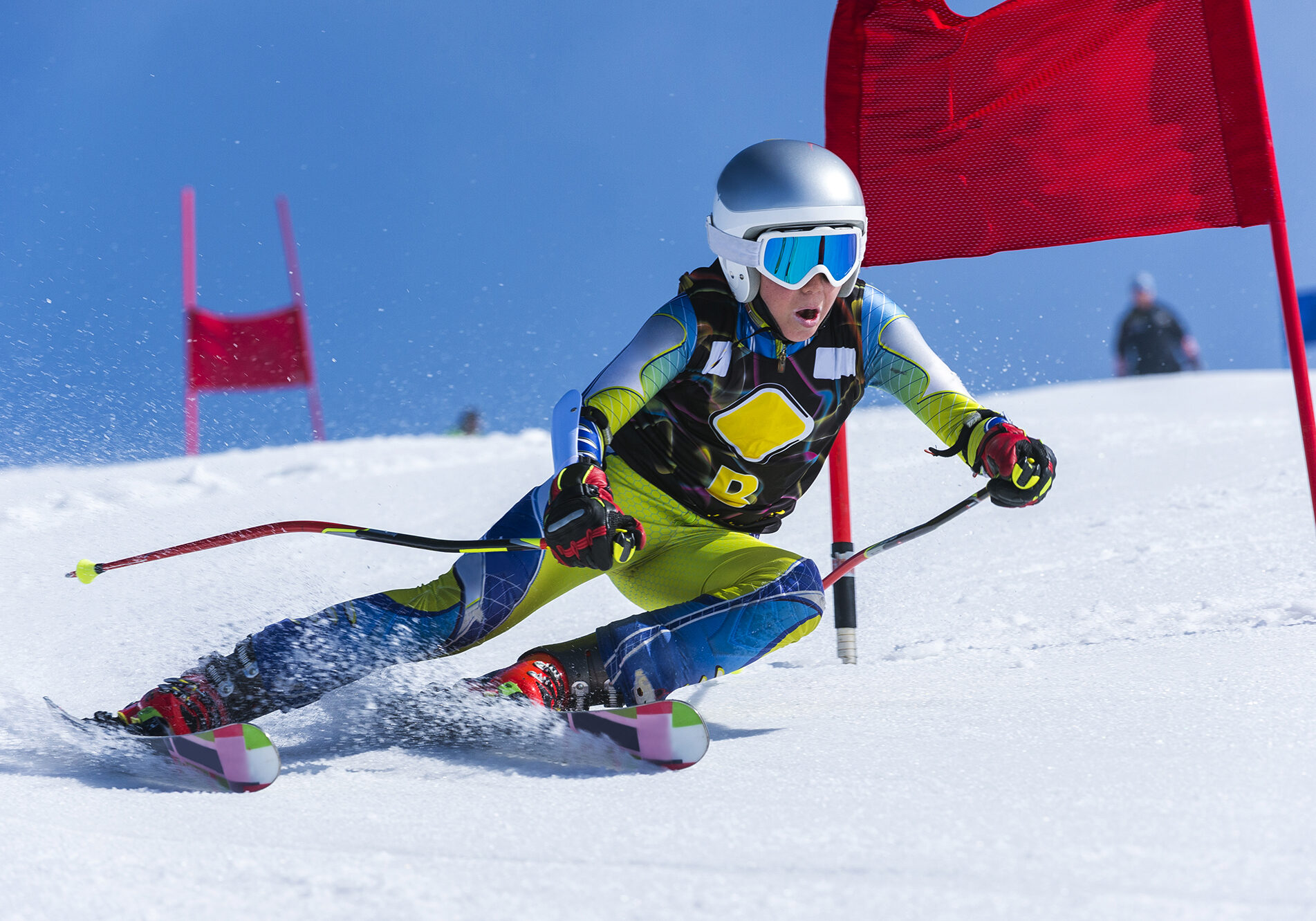 Front view of young male skier passing the red gate, giant slalom teenagers competition