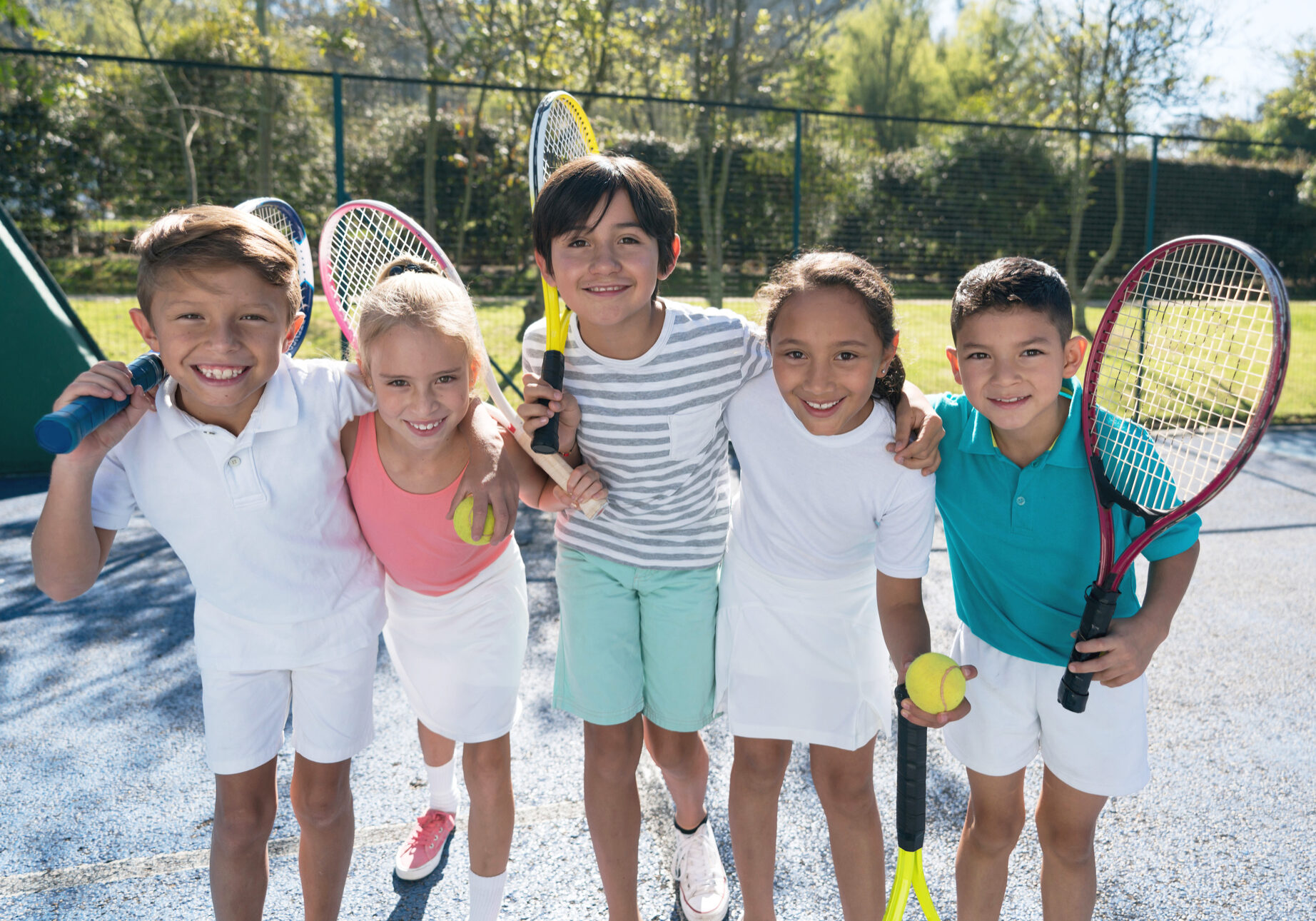 Group of children at the tennis court embracing each other and holding their rackets looking at camera smiling very happy